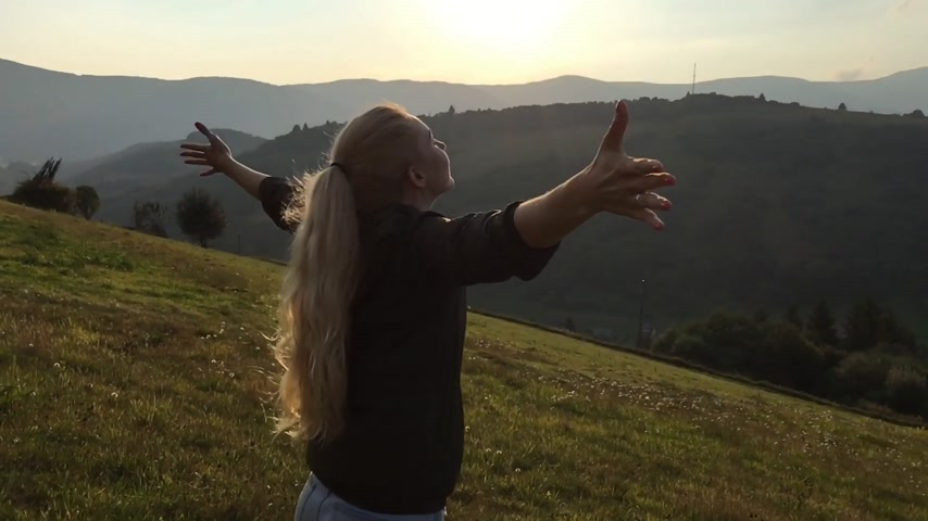 podróżnik : Young woman with long blond pony tail open hands and enjoy sunshine on the top of the mountain. Slow motion shot.