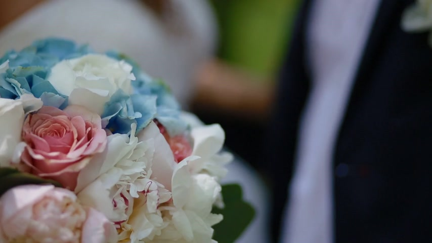 ortanca : Bride and groom pose in the wood. Young man and woman gently look at each other.Beautiful background. Happy moment of loving couple. Footage starts from the closeup shot of the wedding bouquet.