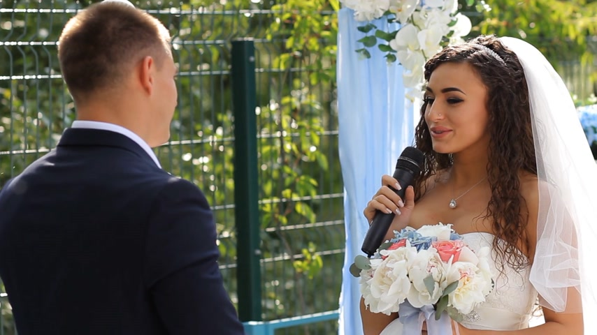 juramento : La novia dice el juramento en la ceremonia de la boda de pie en arco decorado con peonía natural. Archivo de Video