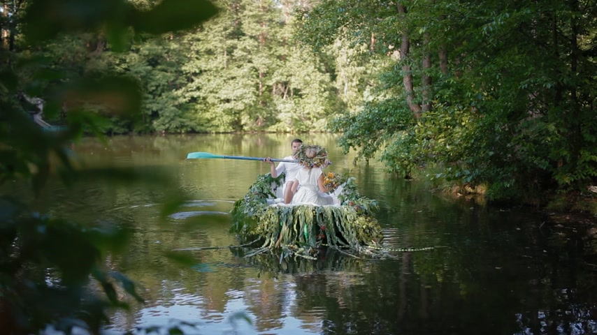 pohanský : KYIV, UKRAINE - 3 July 2015: Young caucasian couple in stylized slavic clothes in the boat decorated with flowers and branches. Ivana Kupala holiday concept.