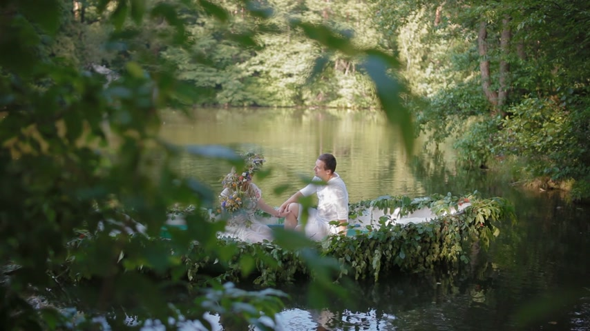 feminity : KYIV, UKRAINE - 3 July 2015: Young caucasian couple in stylized slavic clothes in the boat decorated with flowers and branches. Ivana Kupala holiday concept.