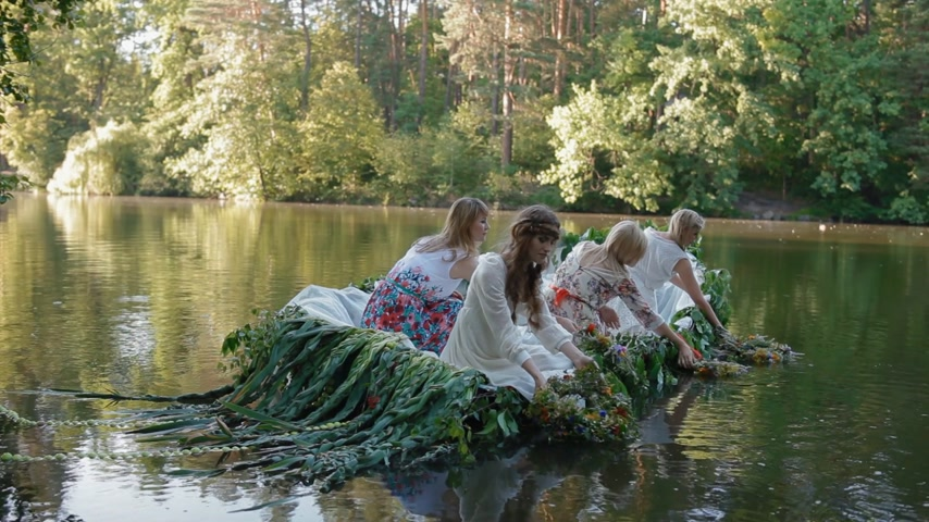 feminity : KYIV, UKRAINE - 3 July 2015: Young women in stylized slavic dress launch wreaths of fresh flower sitting in the boat decorated with branches. Tradition of Ivana Kupala holiday.