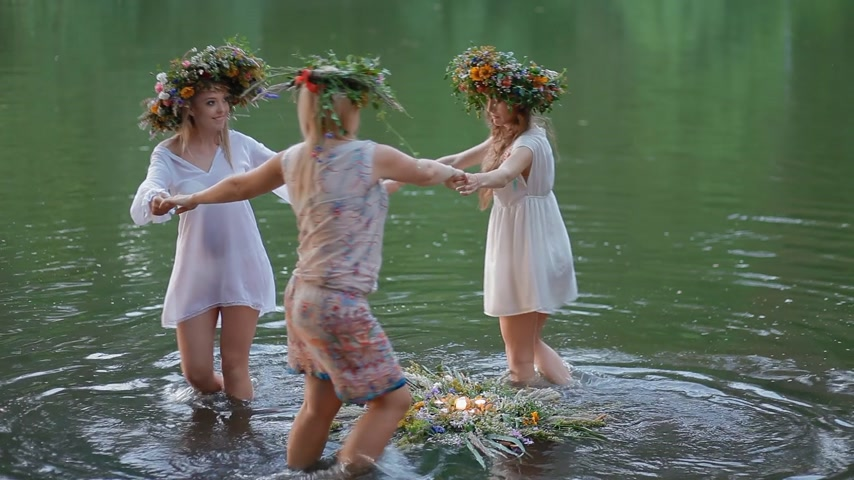 çelenk : KYIV, UKRAINE - 3 July 2015: Women dance in the circle around the wreath on the water holding hands. Beautiful slavic tradition on Kupala holiday.