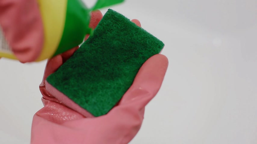 gąbka : A woman in pink rubber gloves pours a cleanser on a sponge. Closeup shot.