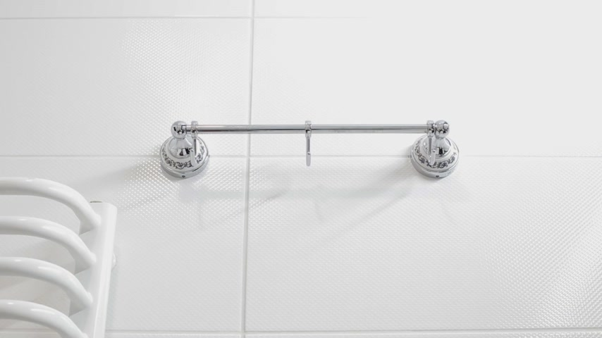 terry : Woman put the white towel on the hanger in the bathroom