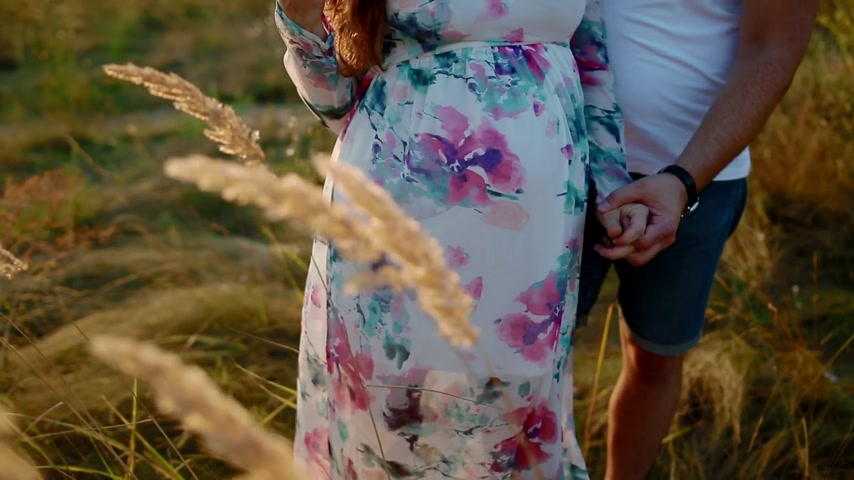 umma : Pregnant white woman in beatiful long dress posing with her husband on the meadow in sunset light. Family values concept.Maternity as a wonderful period of life.