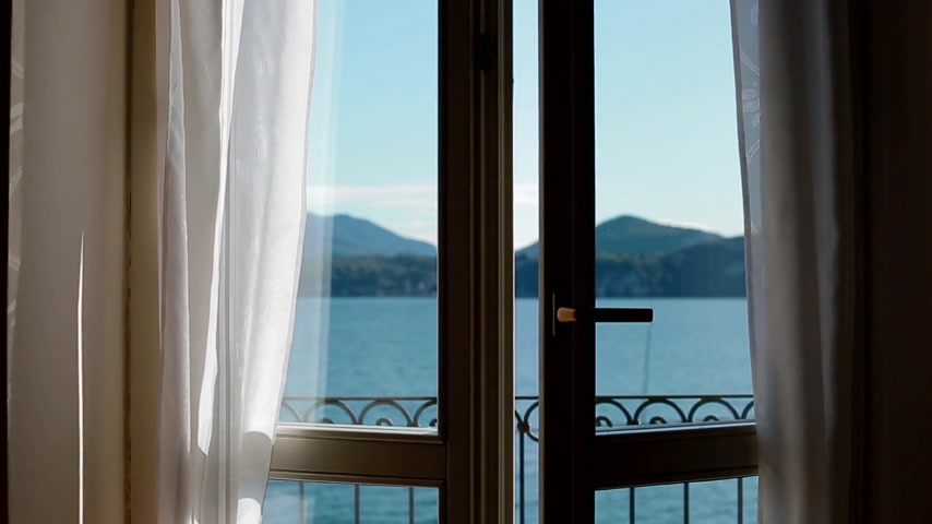 erkély : View of Lago Maggiore through opening window. Chamber influx. Stock mozgókép
