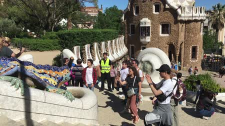 Гауди : BARCELONA, SPAIN - MAY 2017: people take photos near the symbol of Barcelona lizard decorated with mosaic. Overall plan.