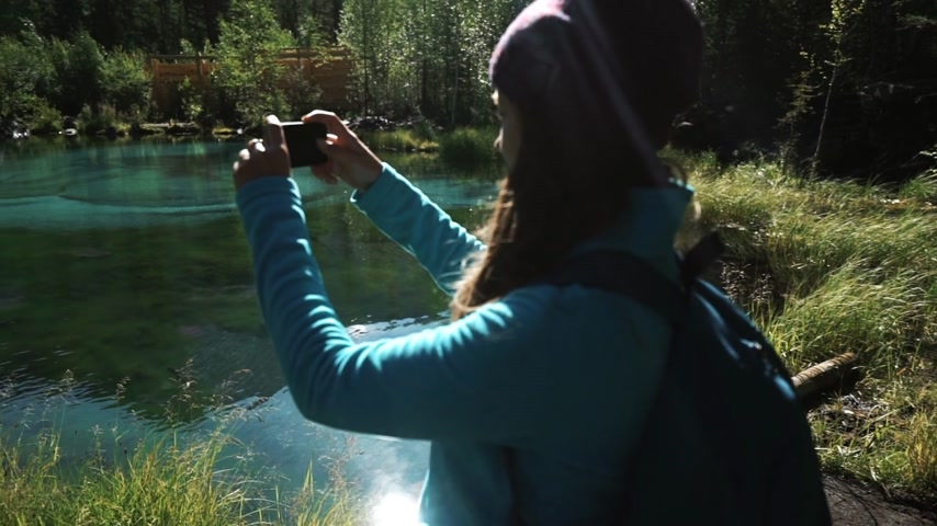 young woman tourist takes a picture on a smartphone on a picturesque blue lake in mountains 50 fps