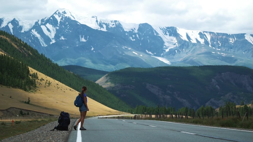 liften : young tourist with a backpack and sunglasses hitchhiking on a mountain road 50 fps