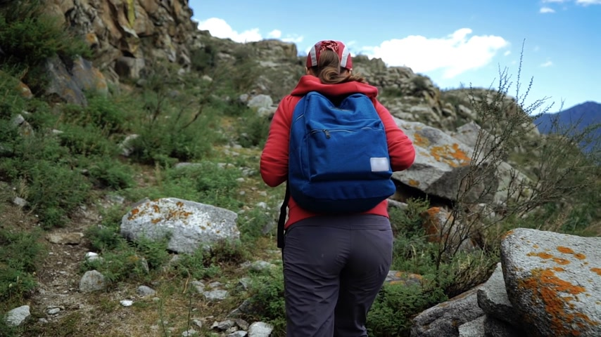 típico : Young tourist woman in cap with backpack climbing stones mountains. Back view