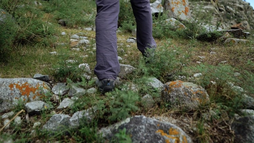 Traveler girl in sneackers climbing stones mountains. Close-up walking legs.