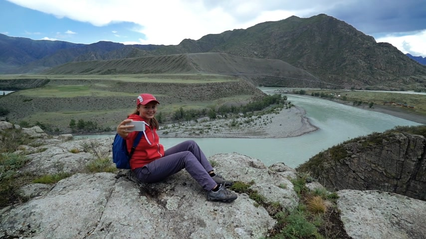 Young woman tourist is sitting on a stone and taking self photo on smartphone. Beautiful mountain and blue mountain river in the background Dostupné videozáznamy
