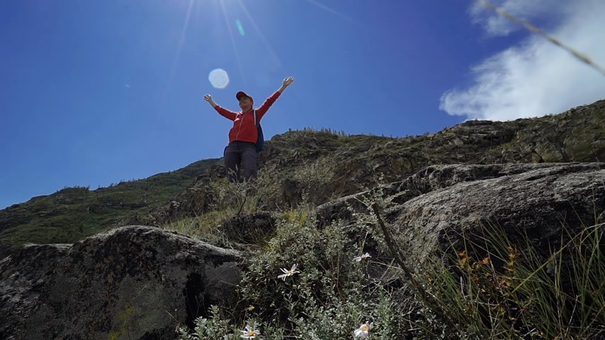 Young happy torist woman with backpack and cap reached up top of mountain and put his hands in the air. Front view, slider
