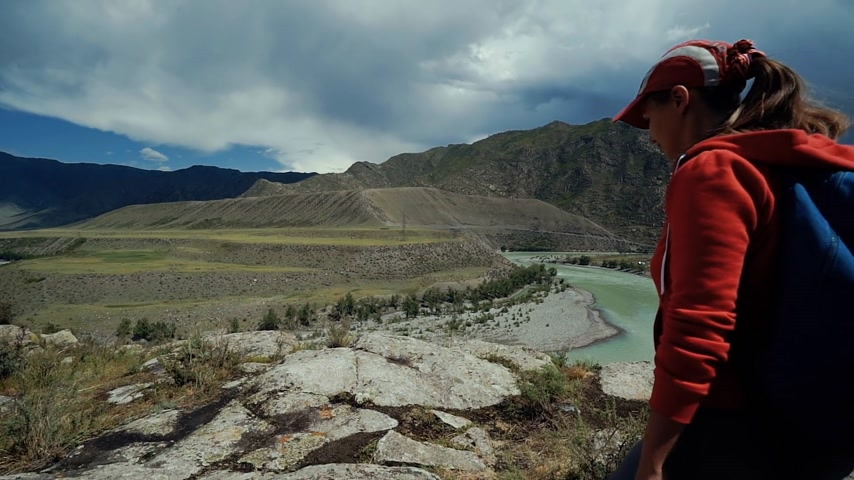 Young happy torist woman with backpack and cap reaches to the edge of the mountain and puts his hands in the air. Back view, slider