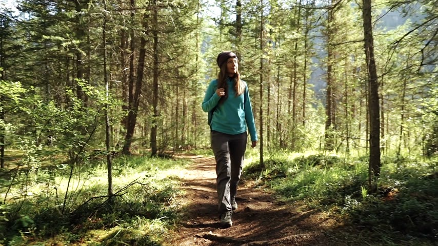 Young woman tourist is walking in the forest on sunny day. Front view