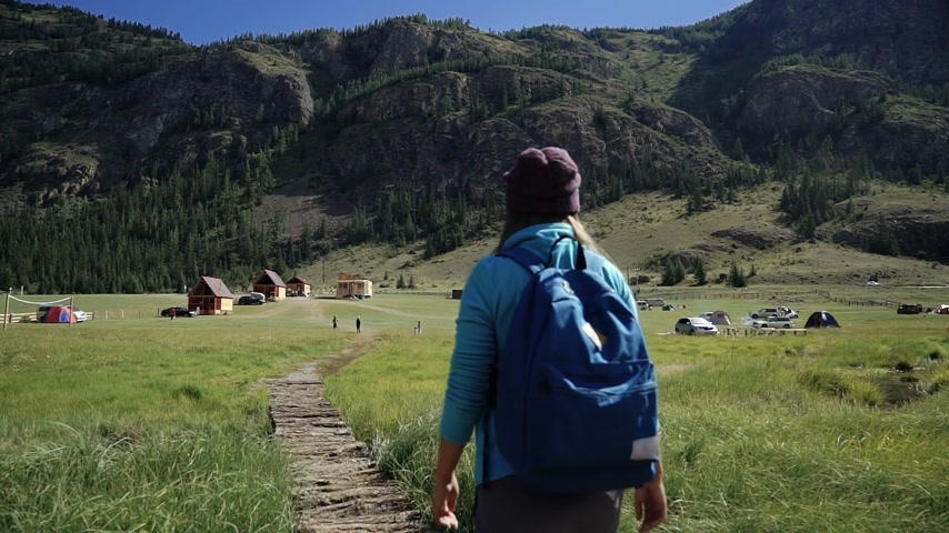 Hiking. Traveler girl with backpack and hat walking on a bridge in the mountains. Camping is in the distance. Adventure in a hike. Back view Стоковые видеозаписи