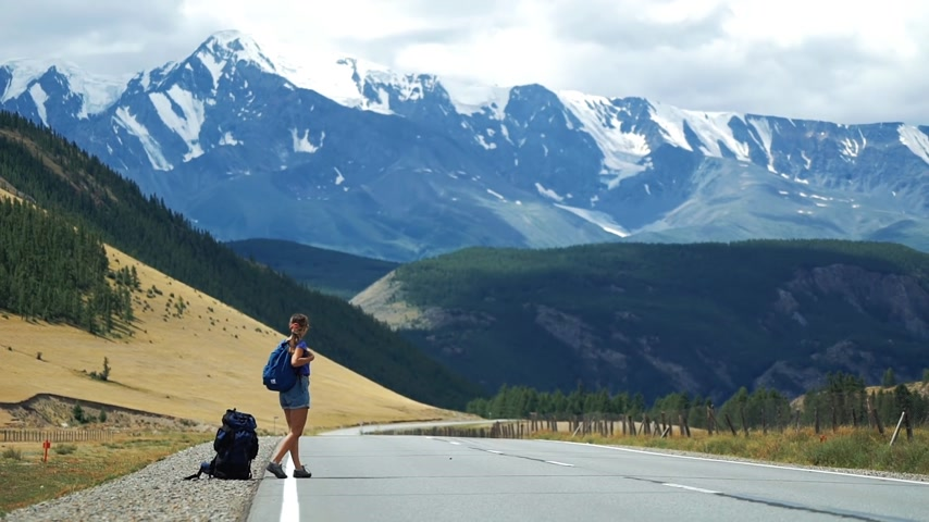 országúti : Young tourist woman with a backpack and sunglasses is hitchhiking on a mountain road. There are snow mountains in the background. Long shot