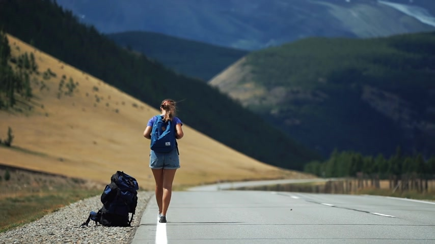 Traveler girl with a backpack and sunglasses is hitchhiking on a mountain road. There are snow mountains in the background. Back view Wideo