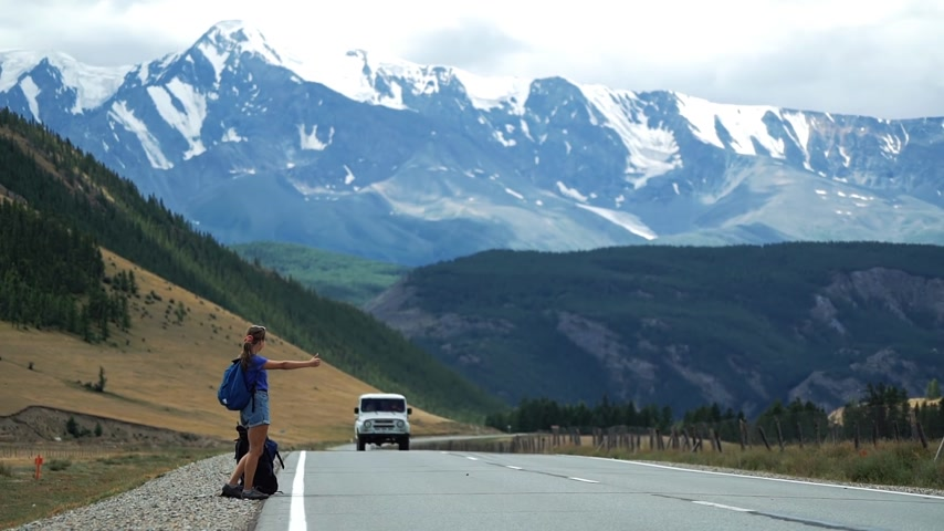 Young tourist woman with a backpack and in shorts is hitchhiking a passing car on a mountain road. There are snow mountains in the background. Long shot Wideo