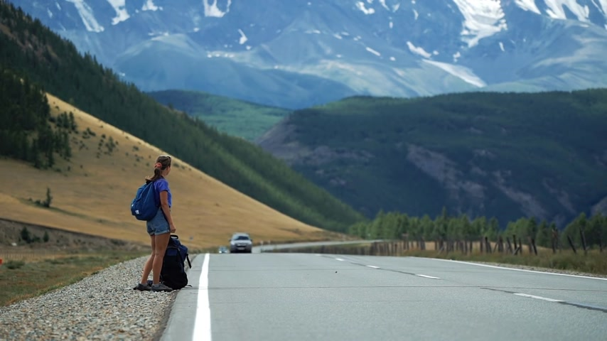 Traveler girl with a backpack and in shorts is hitchhiking a passing car on a mountain road. There are snow mountains in the background
