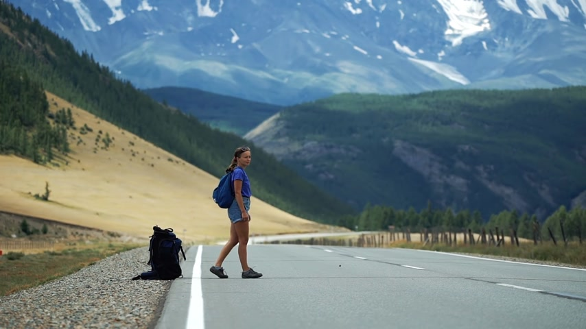Woman hitchhiker is long waiting for cars and kicks a backpack on a mountain road. There are snow mountains in the background