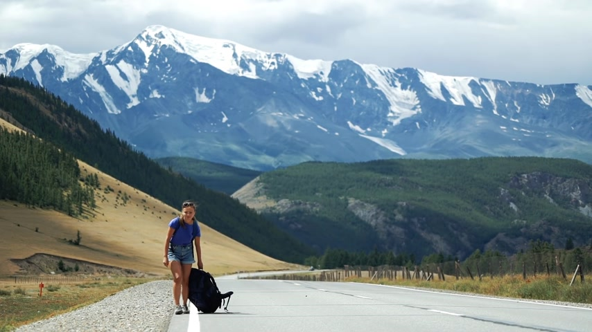 Young tourist woman hitchhiker is pulling a heavy backpack on a mountain road. There are snow mountains in the background. Dostupné videozáznamy