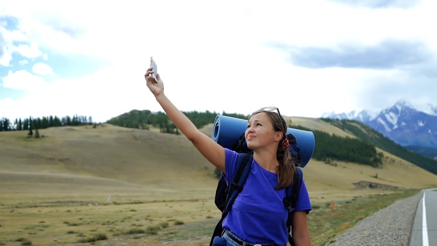 Young tourist woman with a backpack and sunglasses is trying to catch the phone signal on a mountain road. There are snow mountains in the background