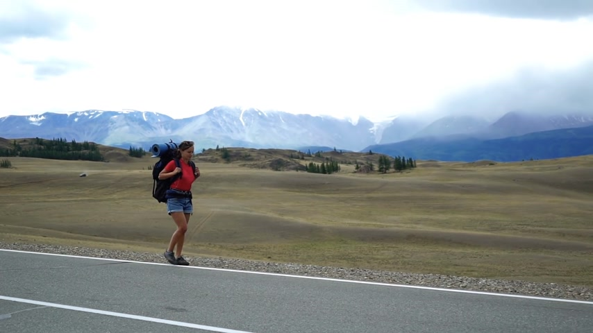Traveler girl with a backpack is walking on the side of the mountain road. There are snow mountains in the background. Long shot Wideo