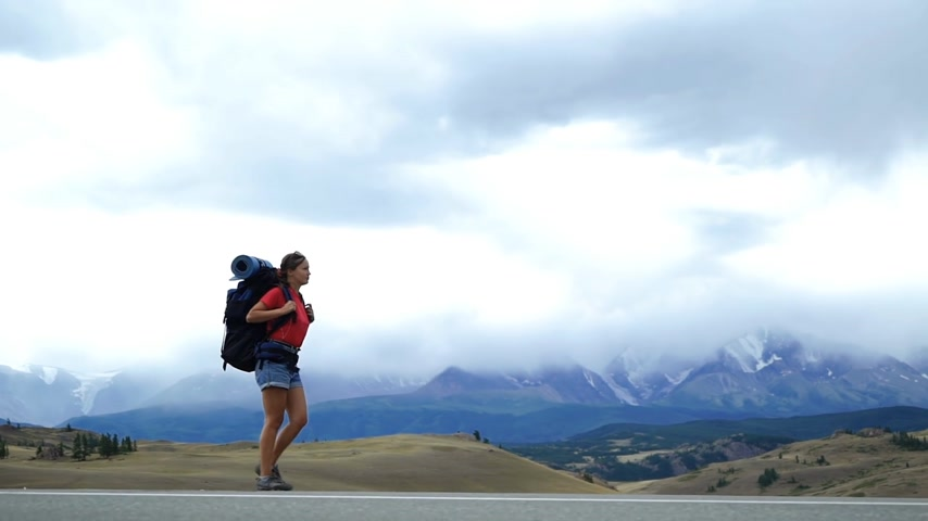 Young tourist woman with a backpack is walking on the side of the mountain road. There are snow mountains in the background. Long shot