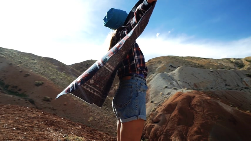 rövidnadrág : Young woman tourist in pattern coat is standing at the edge of red mountain and spread her arms as wings. She wants to fly because of this beautiful view. Coat is developed in the wind. Back view Stock mozgókép