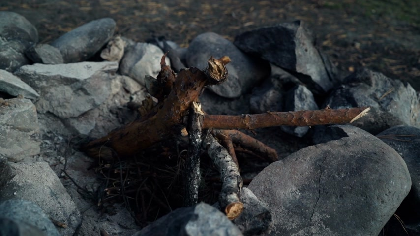 生存 : Man tourist buit a fire on a stone by the flint in evening. Close up arms