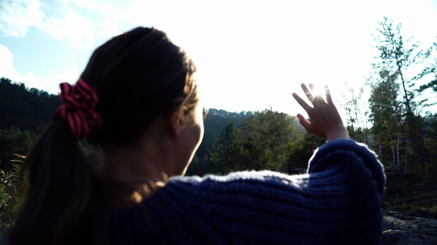 Young woman looks at the sun through the hand. Back view
