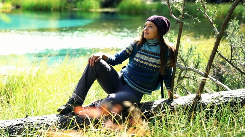 сибирский : Beautiful tourist woman with backpack in warm sweater and hat sits on a fallen tree by mountain lake. Front view