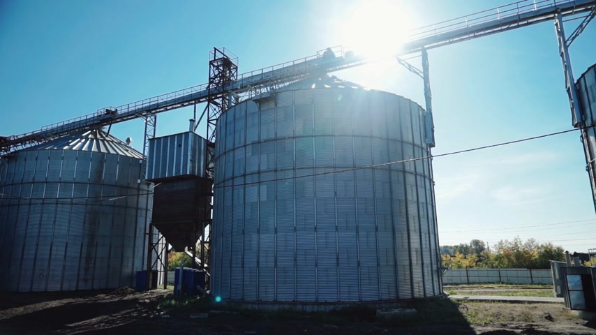 Modern metal grain elevators standing on grain farm Wideo
