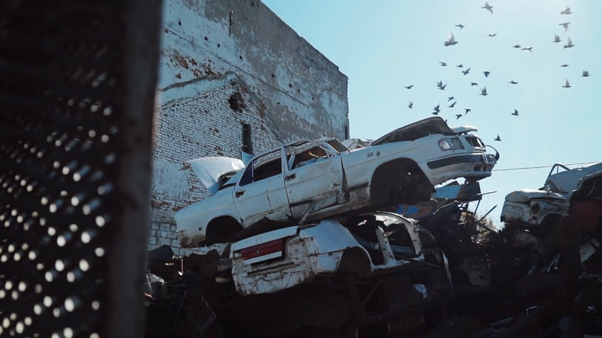 graveyard of cars on the metal scrap yard, birds fly in the sky Wideo