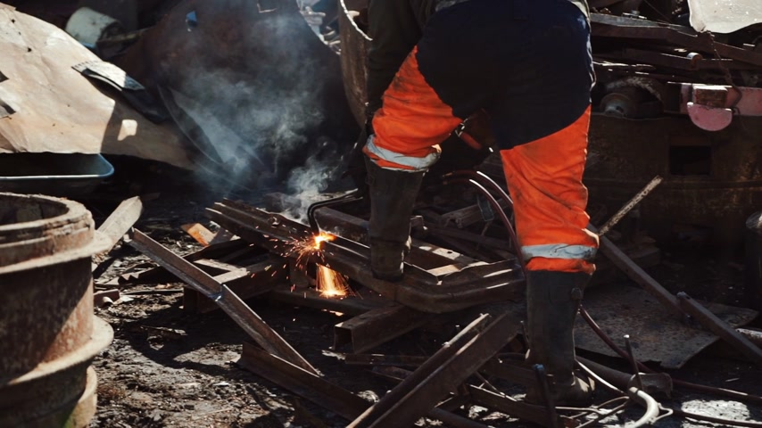 Worker cuts rusty metal with a gas cutter on a scrap dump Wideo