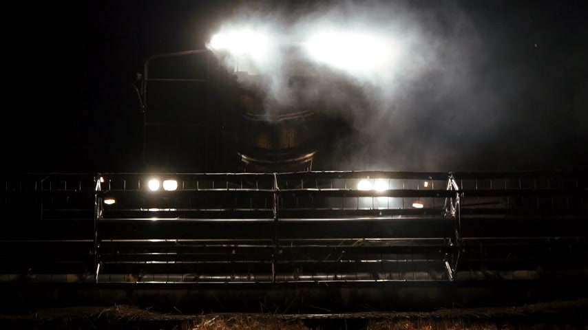 soy : close-up modern combine reaper at night harvesting, front view