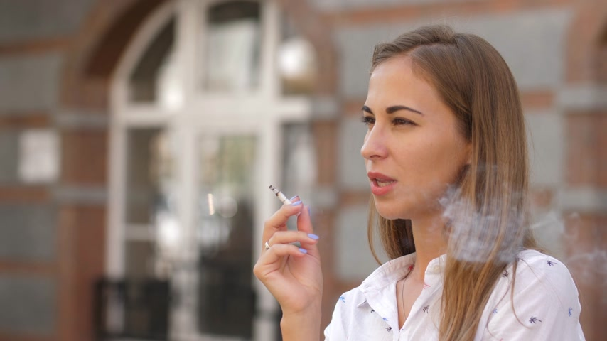 sosyal konular : Young beautiful woman smokes on the street. 4k. slow motion Stok Video