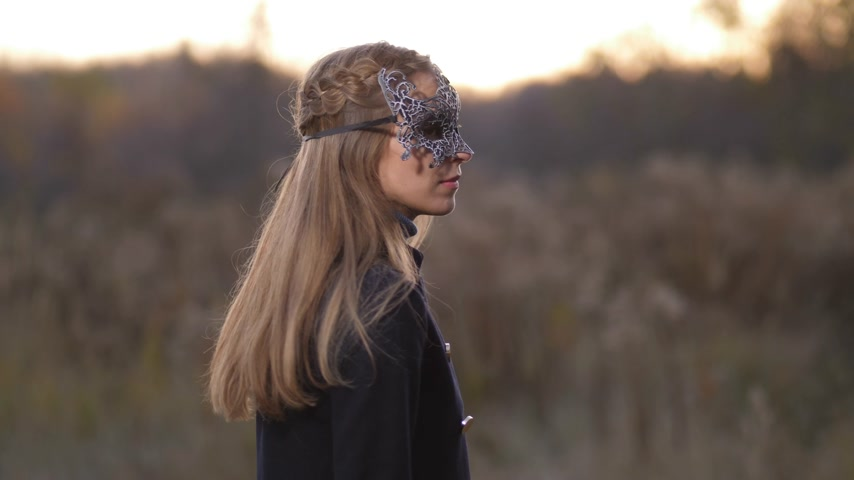 extreme close up : Close-up, a girl in a beautiful mask makes a kiss at the camera. Everything happens in the fall on the field against the sunset 4K Slow Mo