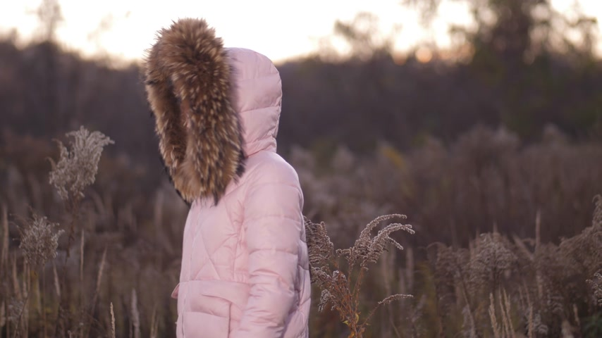 yelow : There is a girl in the park behind her. She is dressed in a pink down jacket, on the head of the hood. The girl turns around, instead of the face of the tigers mask 4K Slow Mo