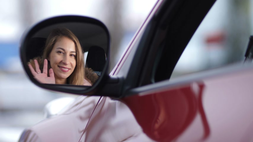 bok : Pretty girl lowers the window in the car, looks in the side mirror, waves her hand and smiles 4K Slow Mo