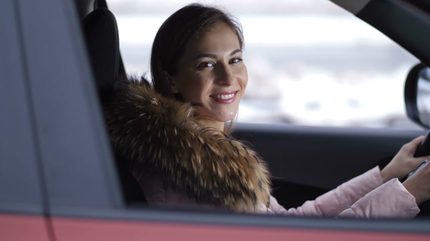 kap : A beautiful girl drives a car, stops, smiles and drives off 4K Slow Mo