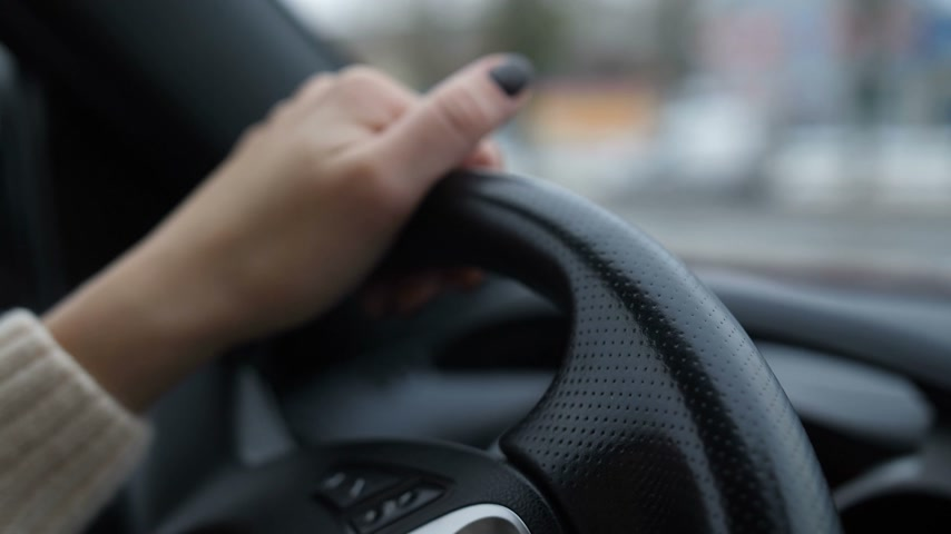final destination : Close-up. Womens hands on the wheel, the girl is fun, during the ride, the fingers play a tune, a good mood 4K Slow Mo Stock Footage