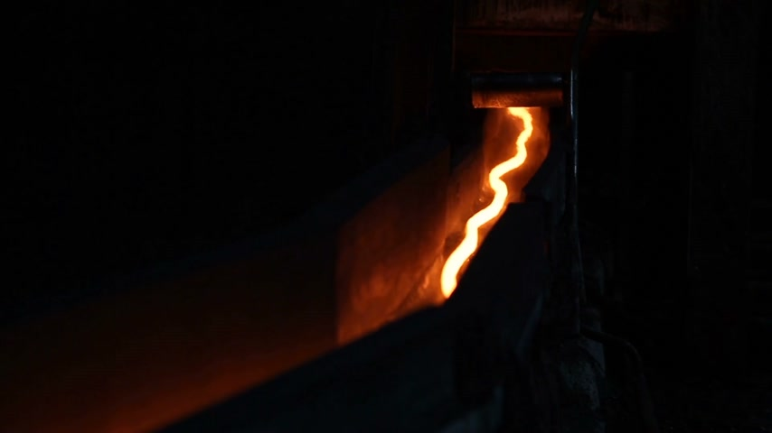 minério : A thin thread of hot steel, like a snake crawling through the tunnel. Metal production.