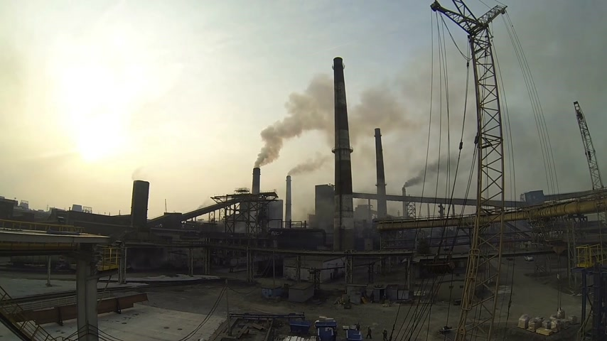 tudo : Timelapse of the territory of the metallurgical plant. Of all the pipes are huge clouds of dirty smoke. At the bottom go plant worker.