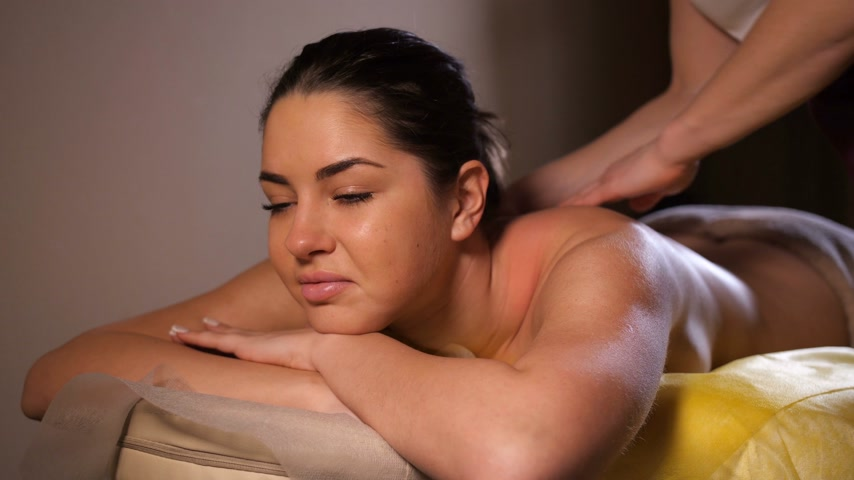 kneads : Masseur kneads the back of a beautiful girl. The girl looks forward and smiles. 4K Slow Mo Stock Footage