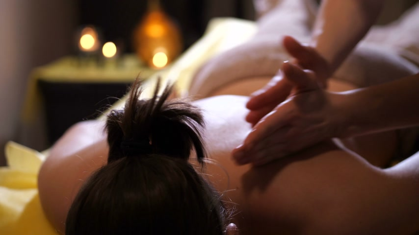 cuidados com a pele : Massage. Hands warm the skin on the female back. 4K Slow Mo Stock Footage