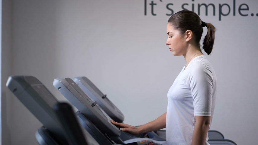 genezing : The girl on the treadmill. First comes, accelerates, starts to run. 4K Slow Mo