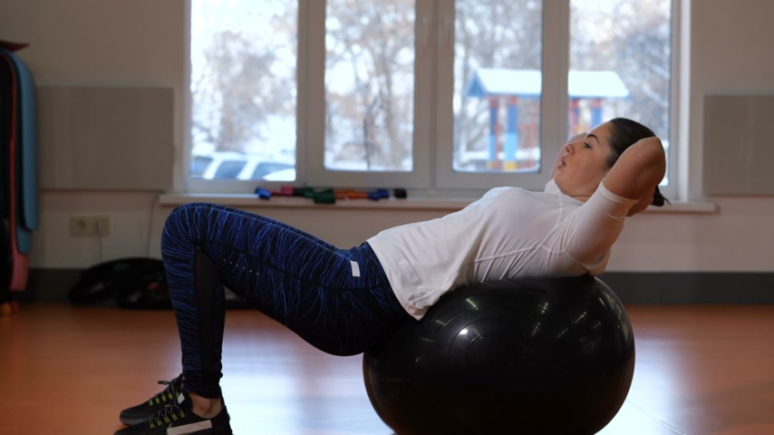 tło : Girl in fitness club shakes press on the ball. 4K Slow Mo